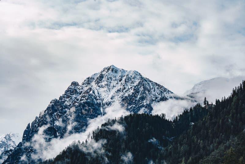 Tiro bonito de montanhas rochosas altas nevoentas e nebulosas imagens de stock royalty free