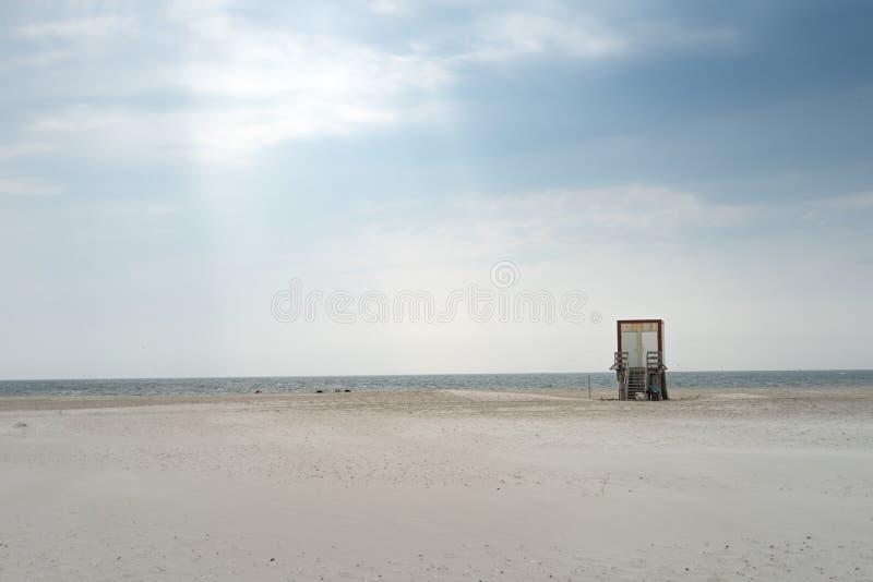 Tiro bonito de um Sandy Beach durante um dia ensolarado calmo com uma estrutura de madeira pequena no local fotografia de stock royalty free