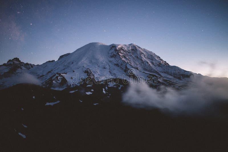 Tiro bonito de uma montanha nevado cercada pela névoa natural com surpresa do céu estrelado fotos de stock
