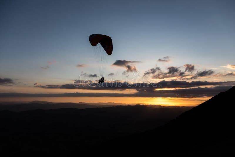 Tiro bonito de uma silhueta do paraglider que voa sobre Monte Cucco Umbria, Itália com por do sol no fundo, com fotografia de stock royalty free