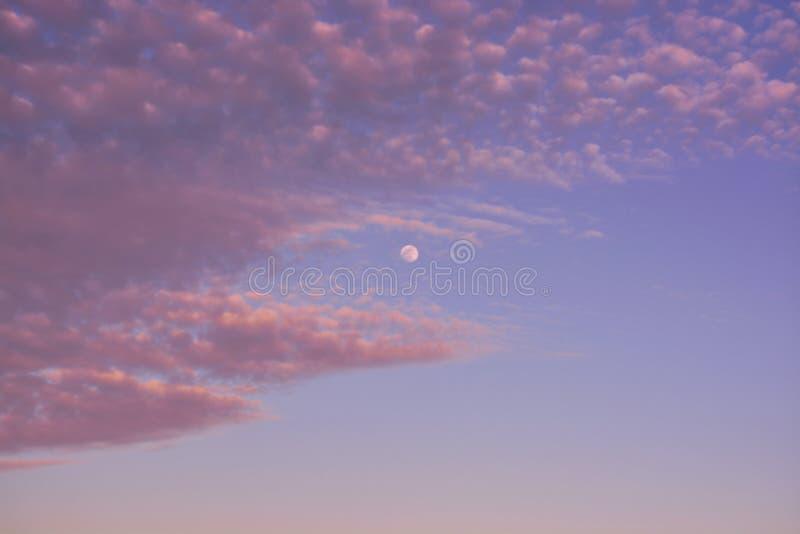Tiro bonito do céu nebuloso acima do oceano com a lua visível entre nuvens fotografia de stock royalty free