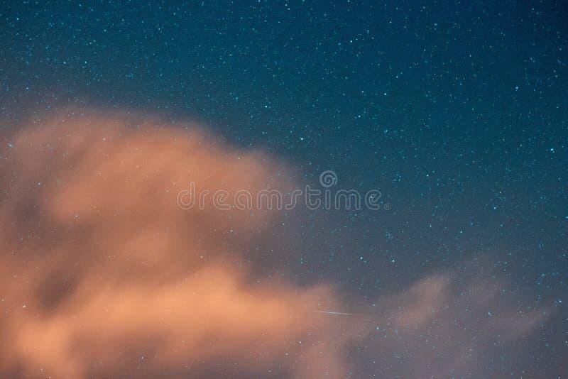 Tiro bonito do céu nebuloso com estrelas de surpresa toda ao redor imagens de stock