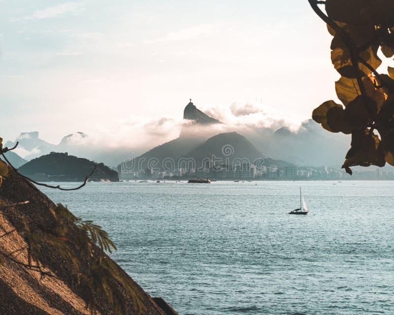 Tiro bonito do mar com um barco na água e nos montes nebulosos de surpresa no fundo imagens de stock royalty free