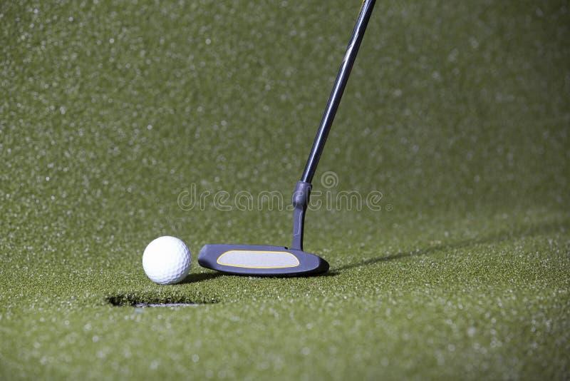 Tiro in buca di golf su un campo verde immagini stock