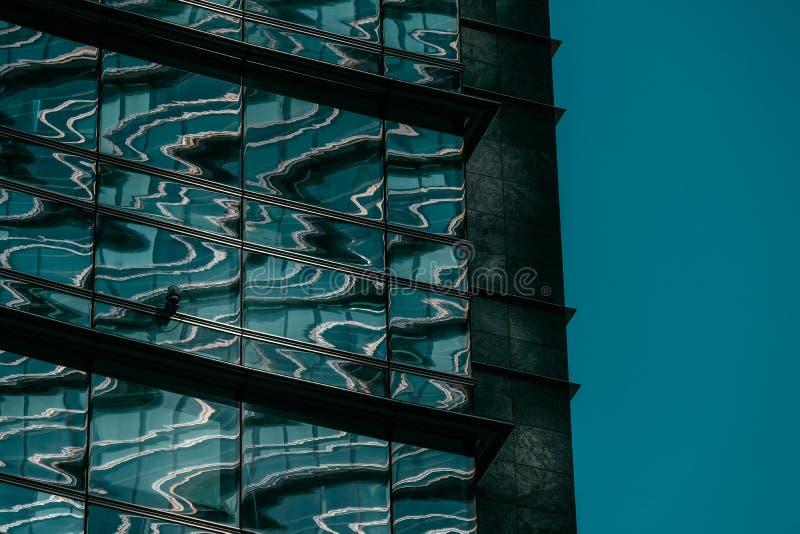 Tiro cercano de un edificio de cristal con una cámara de seguridad y un cielo azul en el fondo fotos de archivo libres de regalías