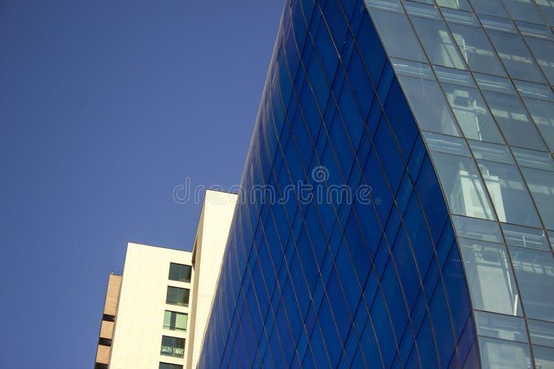 Tiro cercano de una pared azul curvada de la ventana de cristal de un edificio corporativo moderno y elegante foto de archivo libre de regalías