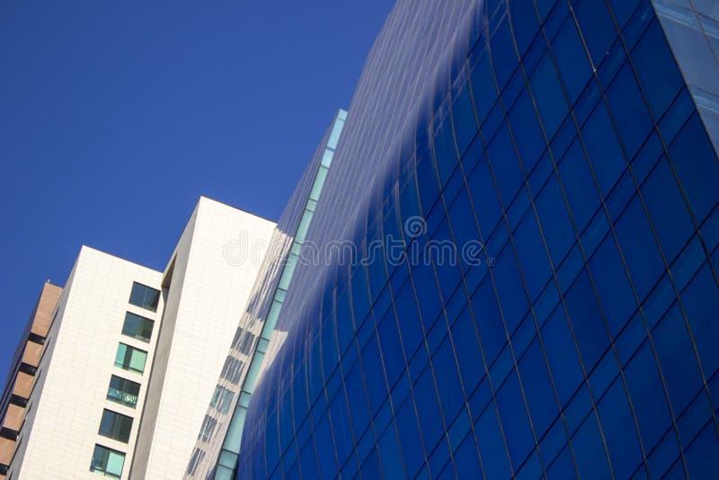 Tiro cercano de una pared azul curvada de la ventana de cristal de un edificio corporativo moderno y elegante, al lado clásico am fotos de archivo