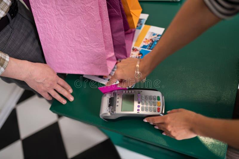 Tiro cercano del cliente que hace el pago con una tarjeta de crédito fotos de archivo