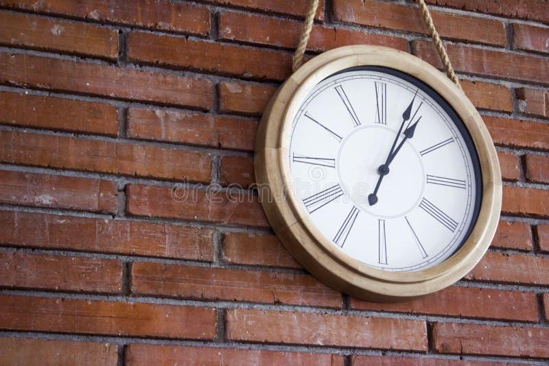 Tiro cercano del medio de un reloj de pared de madera con los números romanos que cuelgan en una pared de ladrillo roja fotos de archivo