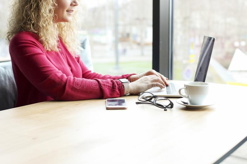Tiro colhido da jovem mulher loura atrativa, sentando-se na cafetaria datilografando no portátil da tela vazia Autônomo fêmea lou fotos de stock royalty free