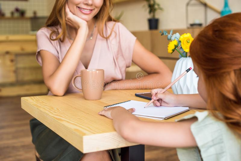 tiro colhido da mãe nova de sorriso que olha o desenho pequeno bonito da filha com lápis imagens de stock royalty free