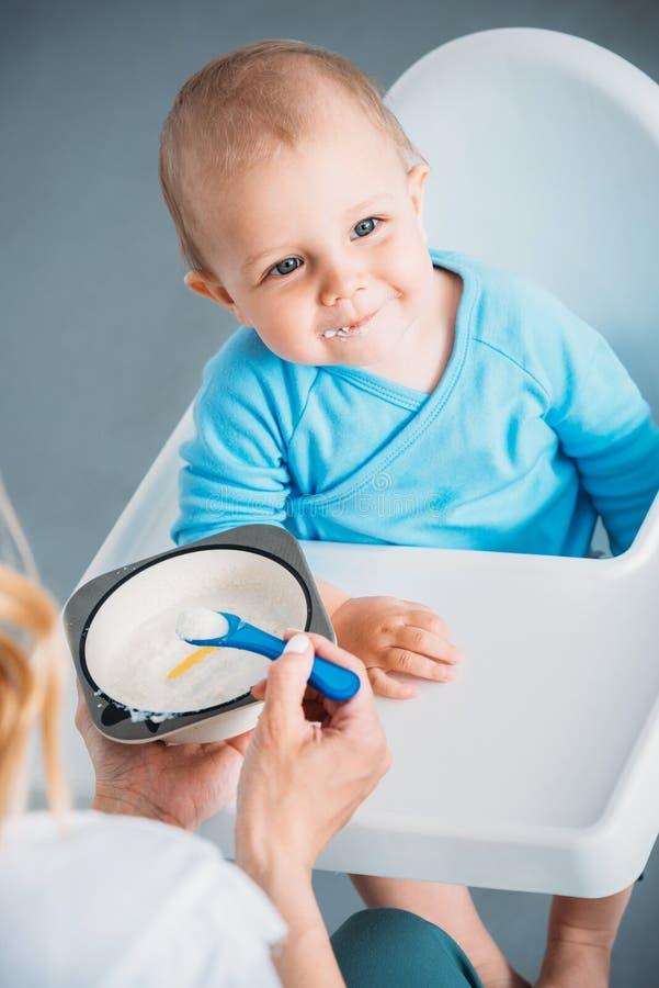 tiro colhido da mãe que alimenta a criança feliz foto de stock