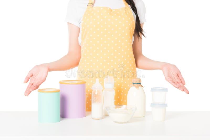 tiro colhido da mulher no avental com os braços largos que estão na tabela com crianças alimento e leite fotografia de stock