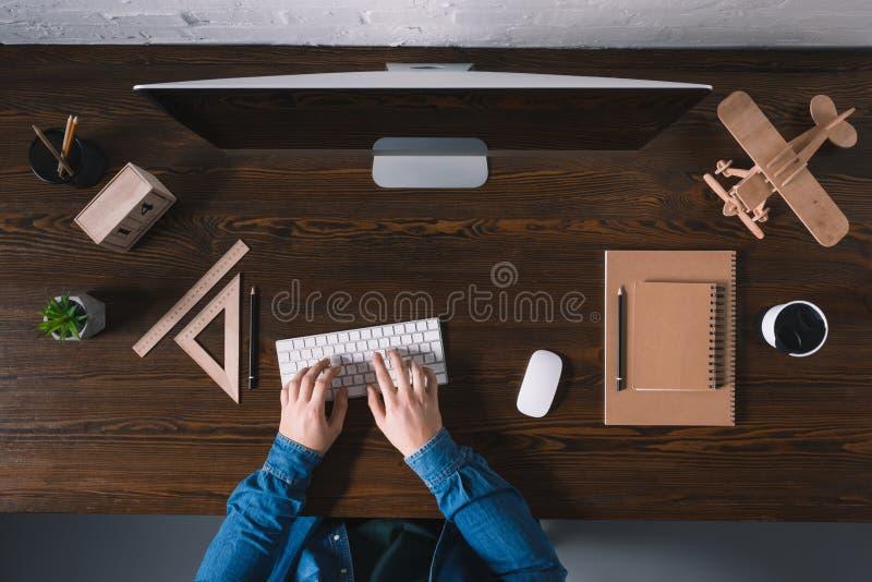 tiro colhido da pessoa que datilografa no teclado e que usa o computador de secretária imagem de stock