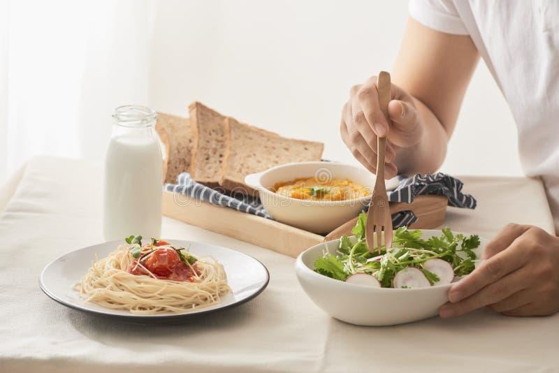 Tiro colhido de masculino comendo o café da manhã com salada, puré da abóbora, espaguetes e leite na tabela na cozinha em casa imagem de stock royalty free