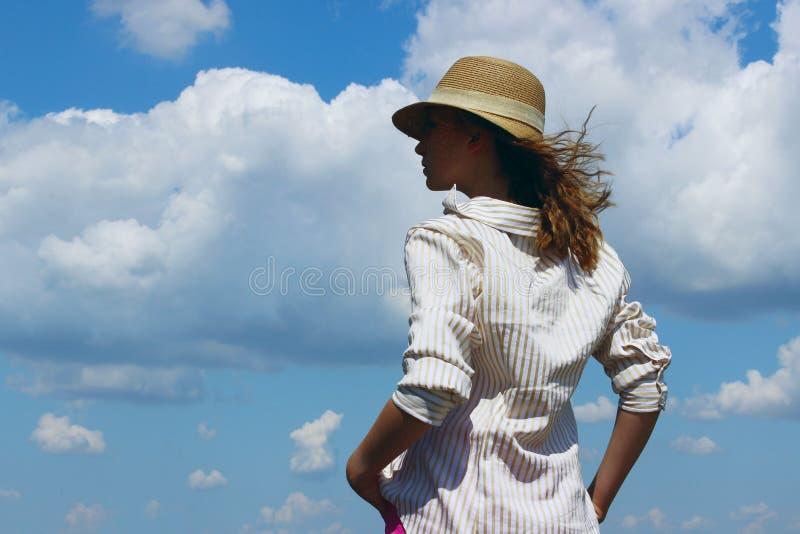 Tiro colhido de uma moça, vestindo um chapéu e uma camisa listrada branca, estando e olhando ao lado sobre o fundo do céu azul Y foto de stock