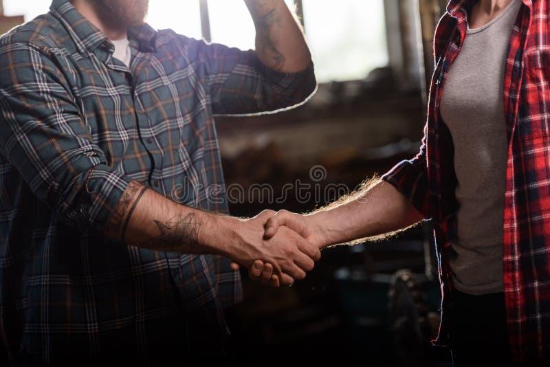 tiro colhido do carpinteiro com a mão tattooed que agita a mão do sócio fotografia de stock royalty free