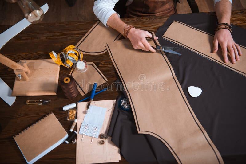tiro colhido do desenhador de moda masculino que trabalha com testes padrões, ferramentas e tela da costura fotografia de stock