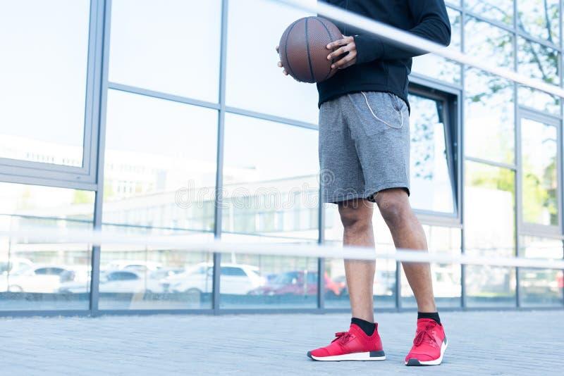 tiro colhido do desportista afro-americano que guarda a bola do basquetebol na rua foto de stock royalty free