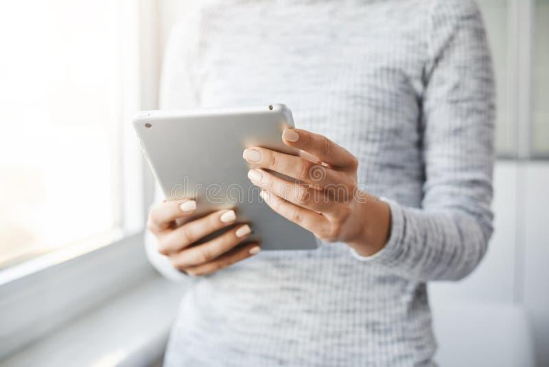 Tiro colhido do empregador que está a janela próxima, guardando a tabuleta digital, lendo a notícia nos meios sociais, verificand fotos de stock