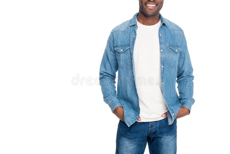 tiro colhido do homem afro-americano de sorriso que está com mãos em uns bolsos imagens de stock royalty free
