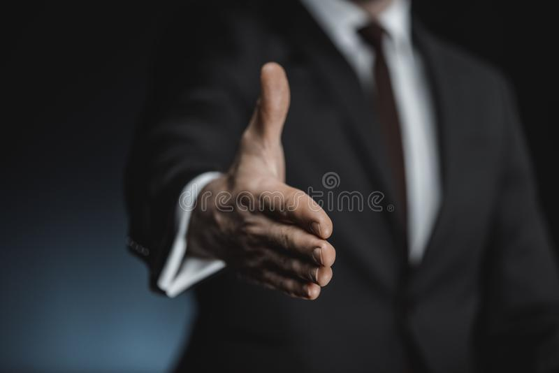 tiro colhido do homem de negócios na mão outstretching do terno imagem de stock royalty free