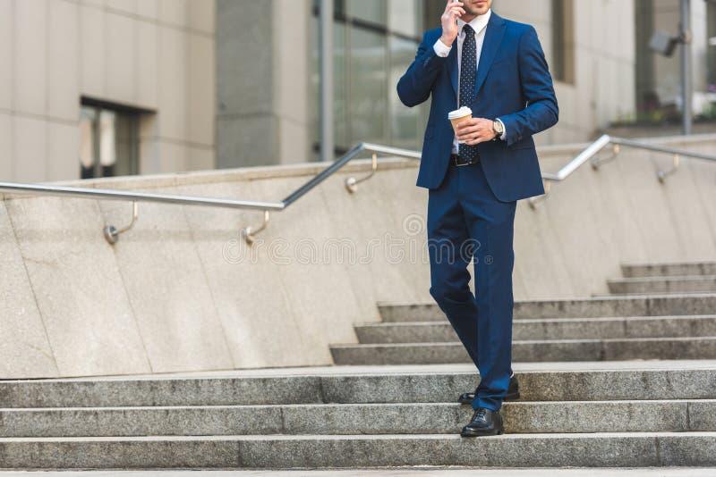 tiro colhido do homem de negócios no terno à moda com o café para ir falar pelo telefone ao andar por escadas imagens de stock royalty free