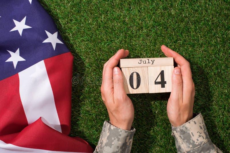 tiro colhido do soldado no uniforme militar que guarda o calendário com data do 4 de julho com a bandeira americana na grama verd foto de stock royalty free