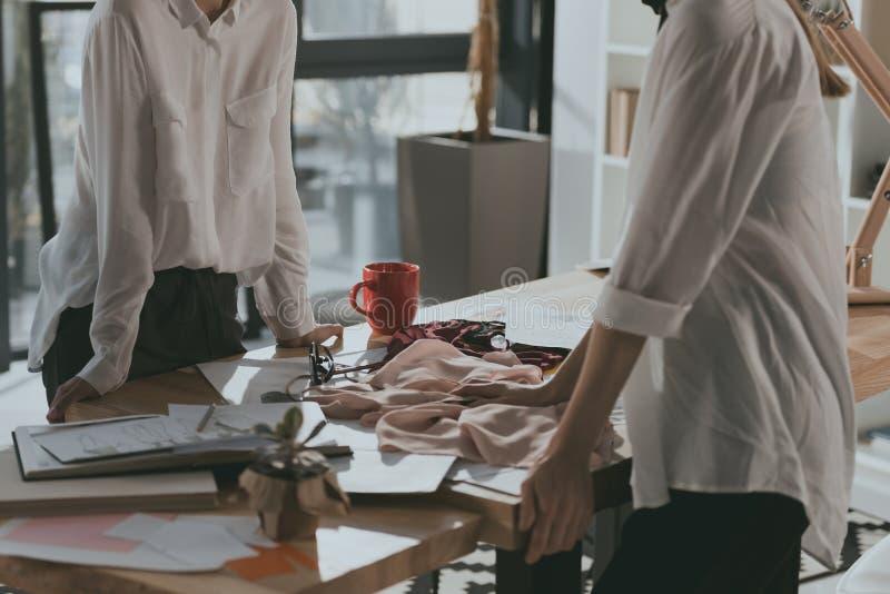 tiro colhido dos desenhadores de moda que trabalham junto foto de stock royalty free