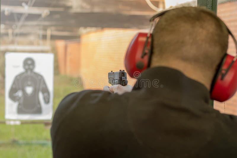 Tiro com uma pistola Pistola do acendimento do homem na escala de tiro fotografia de stock royalty free