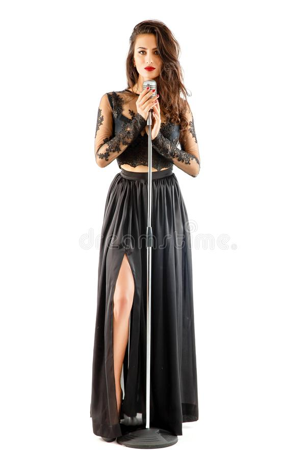 Tiro completo de uma mulher bonita que canta no microfone no isolado branco fotografia de stock royalty free