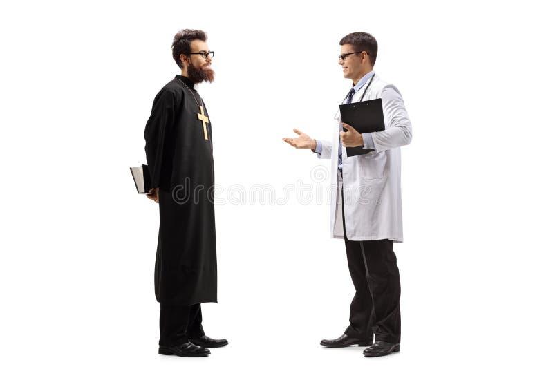 Tiro completo do comprimento de um doutor masculino novo que discusiing algo com um padre imagens de stock