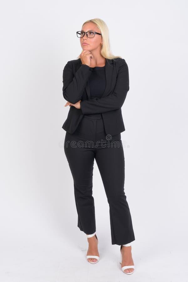 Tiro completo do corpo da mulher de negócios loura nova que pensa e que olha acima imagens de stock royalty free