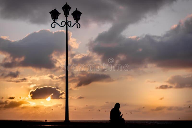 Tiro conceptual y puesta del sol de la silueta de la soledad foto de archivo libre de regalías