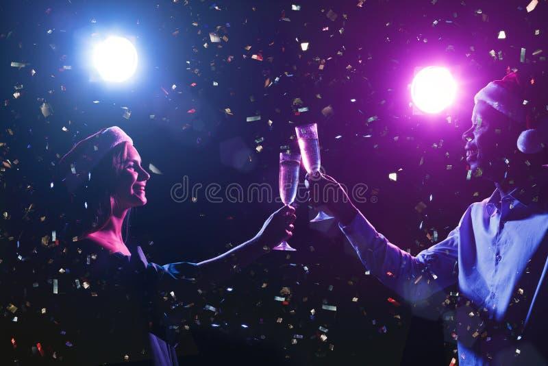 Tiro cosechado de amigos felices en sombreros del satnta con las flautas de champán en el partido del Año Nuevo imagen de archivo libre de regalías