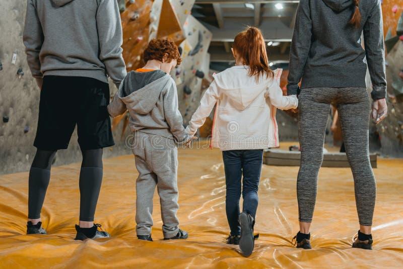 Tiro cosechado de la familia con los niños que llevan a cabo las manos y la situación en fila fotos de archivo