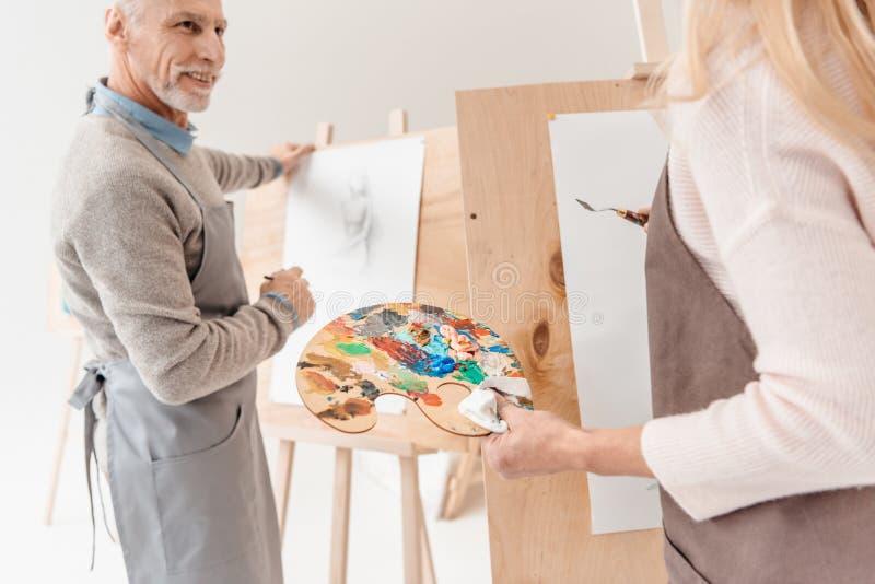 tiro cosechado de la gente mayor que pinta en los caballetes foto de archivo libre de regalías