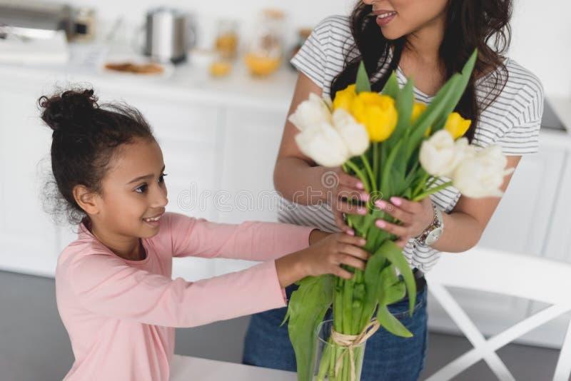 tiro cosechado de la madre y de la hija hermosa que ponen las flores imagen de archivo libre de regalías