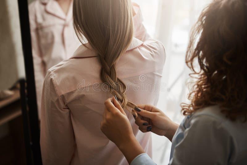Tiro cosechado de la madre y de la hija que se colocan en camisa de dormir mientras que mamá que hace la trenza para su cutie, pe imagen de archivo