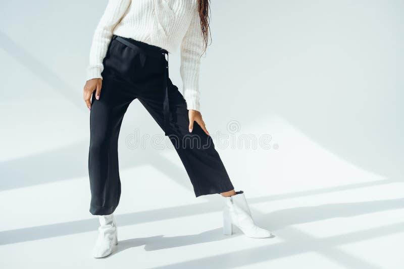 tiro cosechado de la muchacha en pantalones negros de moda y la presentación hecha punto del suéter imagen de archivo