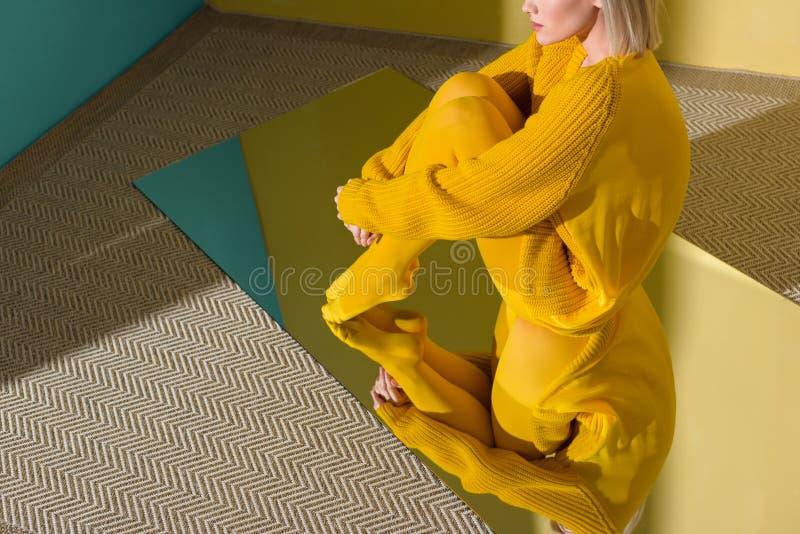 tiro cosechado de la mujer en suéter amarillo y las medias que se sientan en el espejo con la reflexión foto de archivo