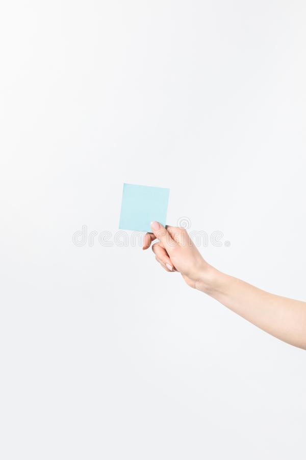 Tiro cosechado de la mujer que lleva a cabo la nota pegajosa azul en blanco disponible imágenes de archivo libres de regalías