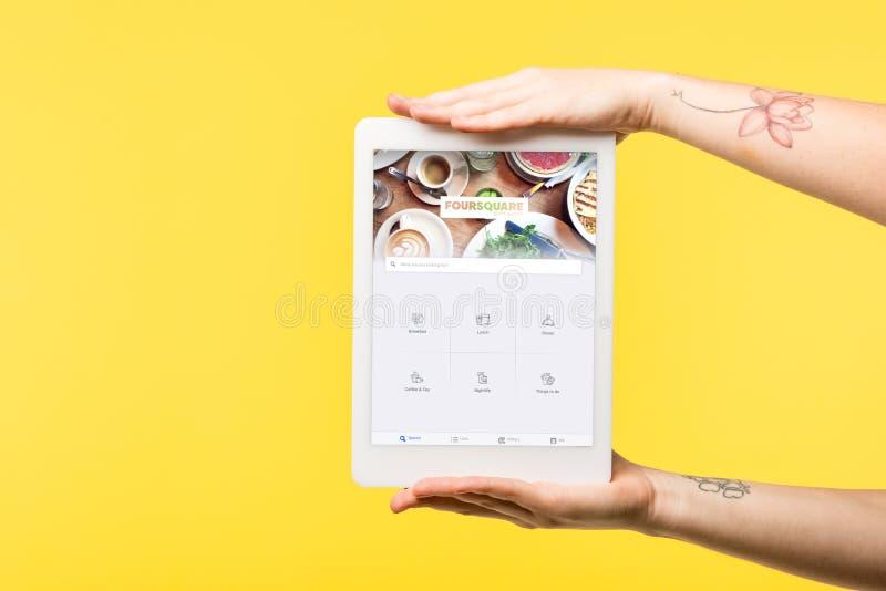 tiro cosechado de la persona que sostiene la tableta digital con página web cuadrada en la pantalla aislada imagen de archivo libre de regalías