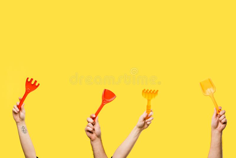 tiro cosechado de las manos masculinas y femeninas que sostienen las palas rojas y amarillas y los rastrillos plásticos aislados foto de archivo