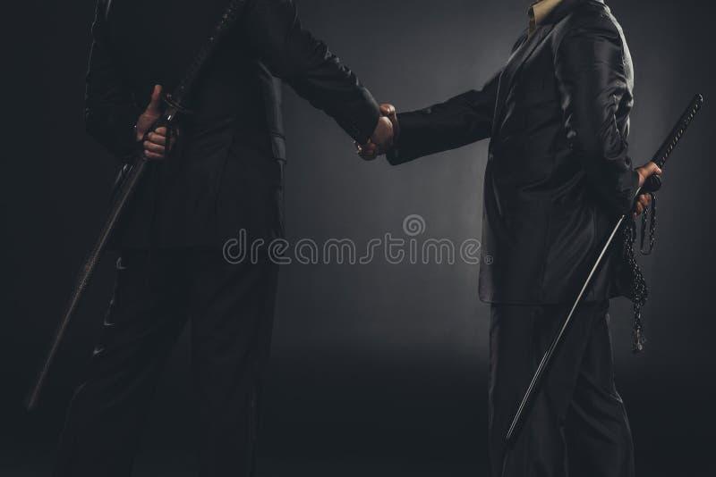 tiro cosechado de los miembros de Yakuza que sacuden las manos con katanas detrás detrás foto de archivo libre de regalías