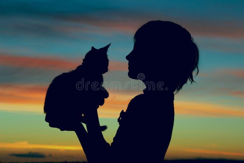 Tiro cosechado de una niña y de un gatito lindos en la puesta del sol fotos de archivo libres de regalías