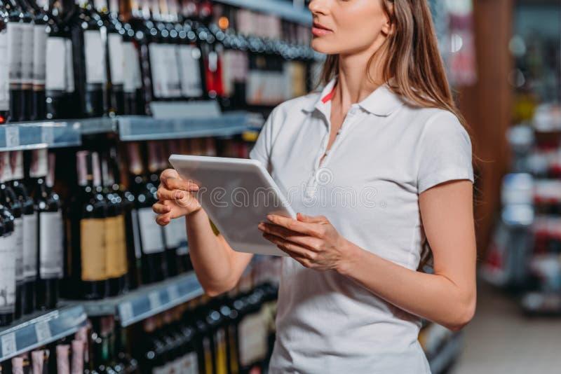 tiro cosechado del ayudante de tienda con la tableta digital imagen de archivo