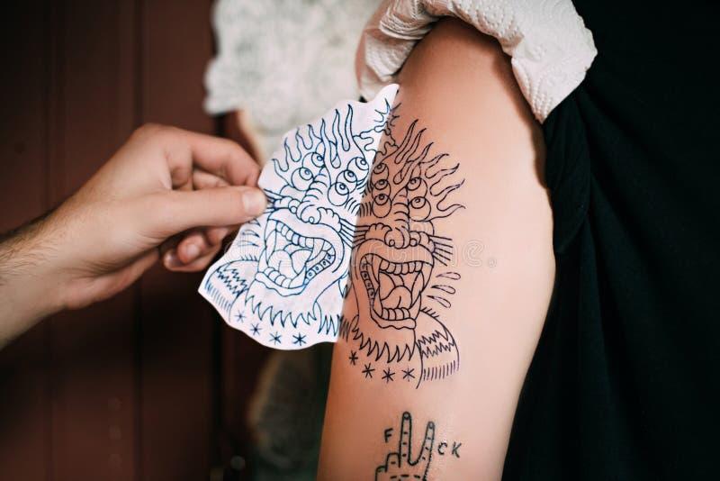 tiro cosechado del bosquejo de transferencia del tatuaje del artista del tatuaje en hombro en tatuaje foto de archivo