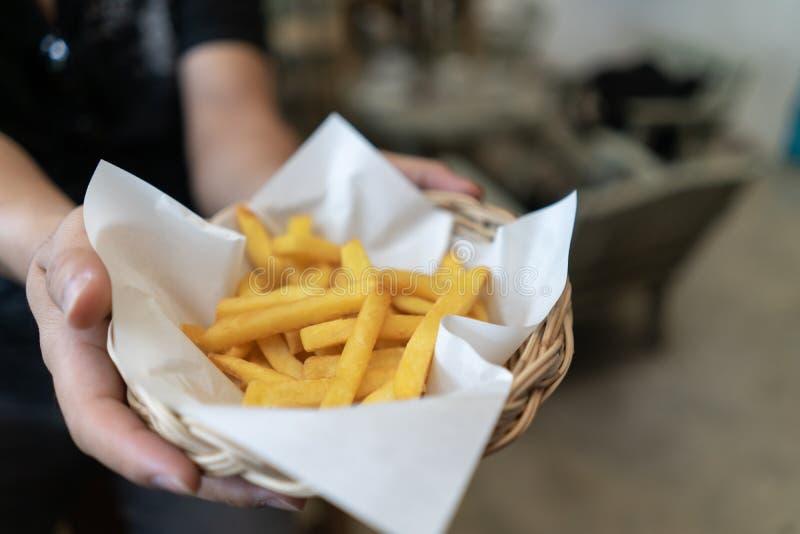 Tiro cosechado del cuenco de la tenencia de la mano del hombre de alimentos de preparación rápida de las patatas fritas en cubo c fotos de archivo