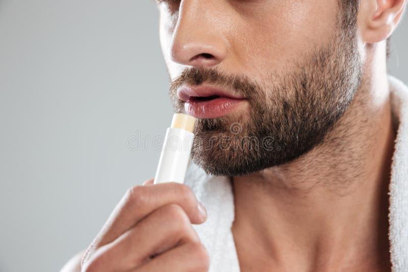 ¿Tiro cosechado del hombre joven con? lápiz labial olorless imagen de archivo libre de regalías